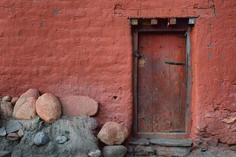 A red ochre wall and old wooden door in Ghami, typical of gompas throughout Upper Mustang.