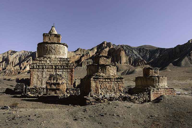 A group of old ochre chortens outside of Ghami, their colours blending seamlessly with the mountains in the background