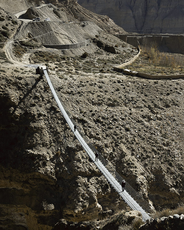 People cross a suspension bridge over a rocky chasm from the village of Ghyakar in Upper Mustang in Nepal