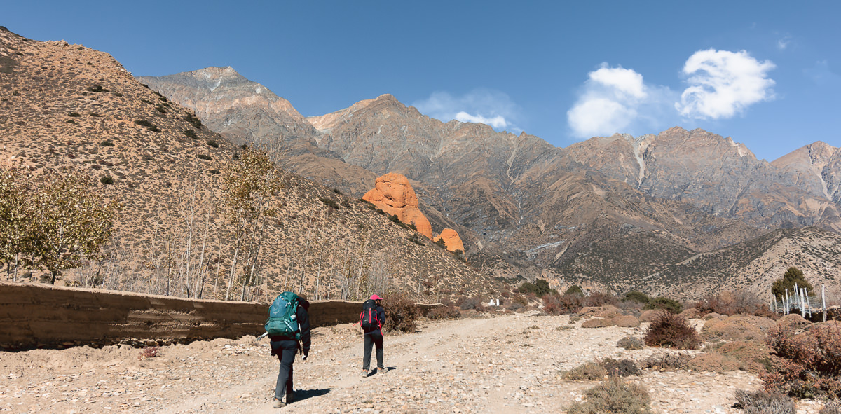 Two hikers on the Upper Mustang trek, climbing a gentle rocky trail towards towering mountains.