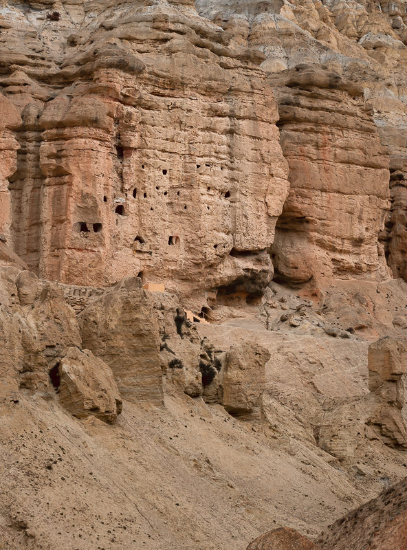 A cliff face pockmarked with holes, forming the Jhong Caves in Upper Mustang