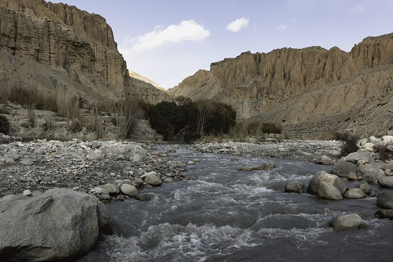 The blue-grey Kali Gandaki river with jagged cliffs rising either side