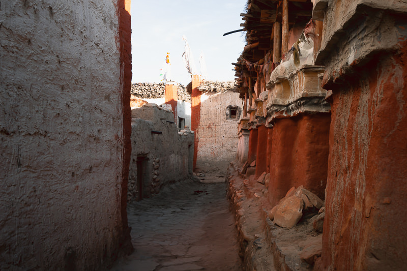 Red chortens and whitewashed walls in a narrow alleyway in Lo Manthang
