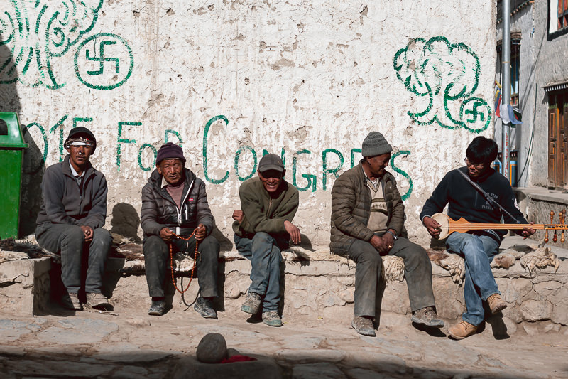 Four older men sit in the afternoon sun in Lo Manthang while a younger man plays a three stringed musical instrument.