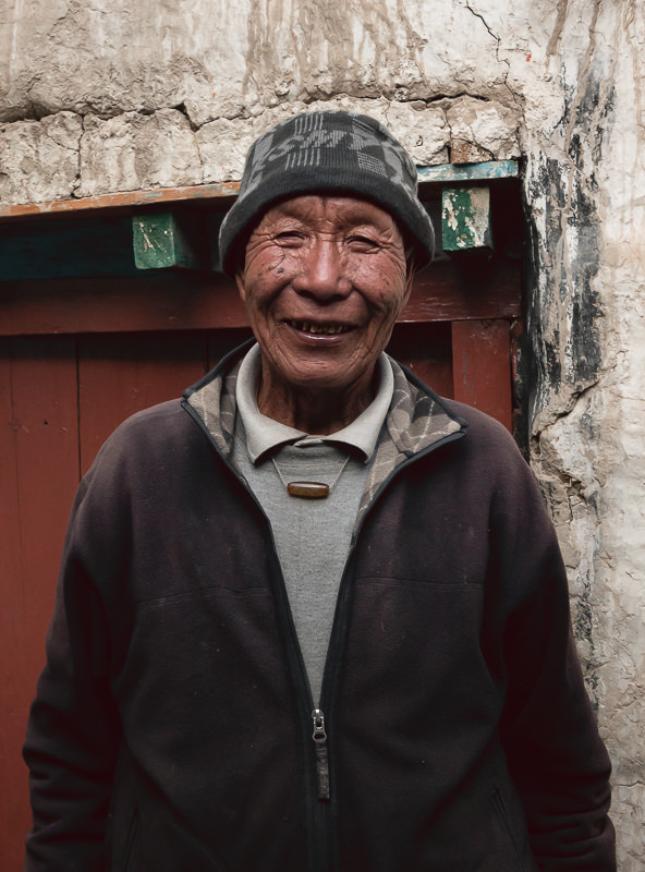 A smiling portrait of an older man and proprietor of a souvenir shop in Lo Manthang