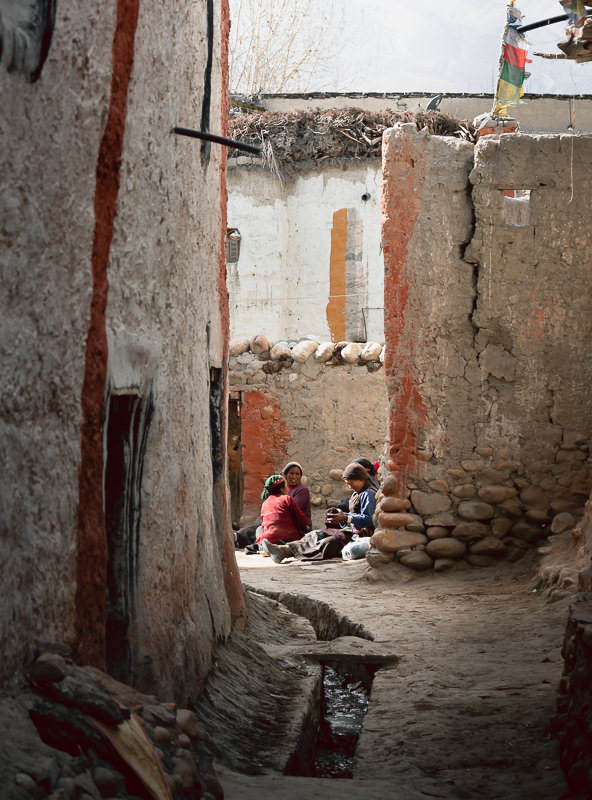 Women sitting on the ground chatting in a narrow alleyway in Lo Manthang