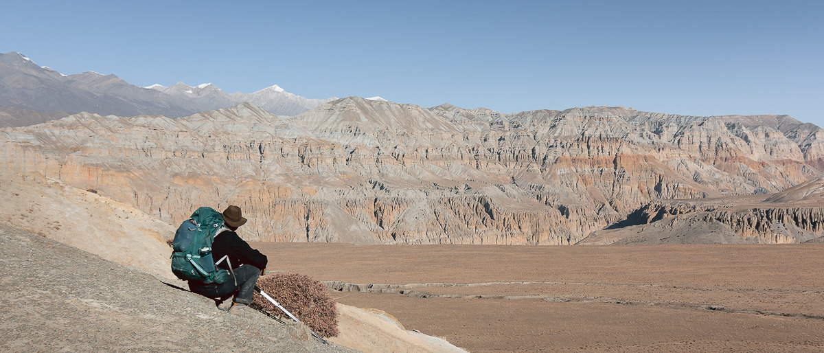 A trekker sitting admiring the view of a flat high plateau and colourful mountain ridge beyond whilst trekking in Upper Mustang
