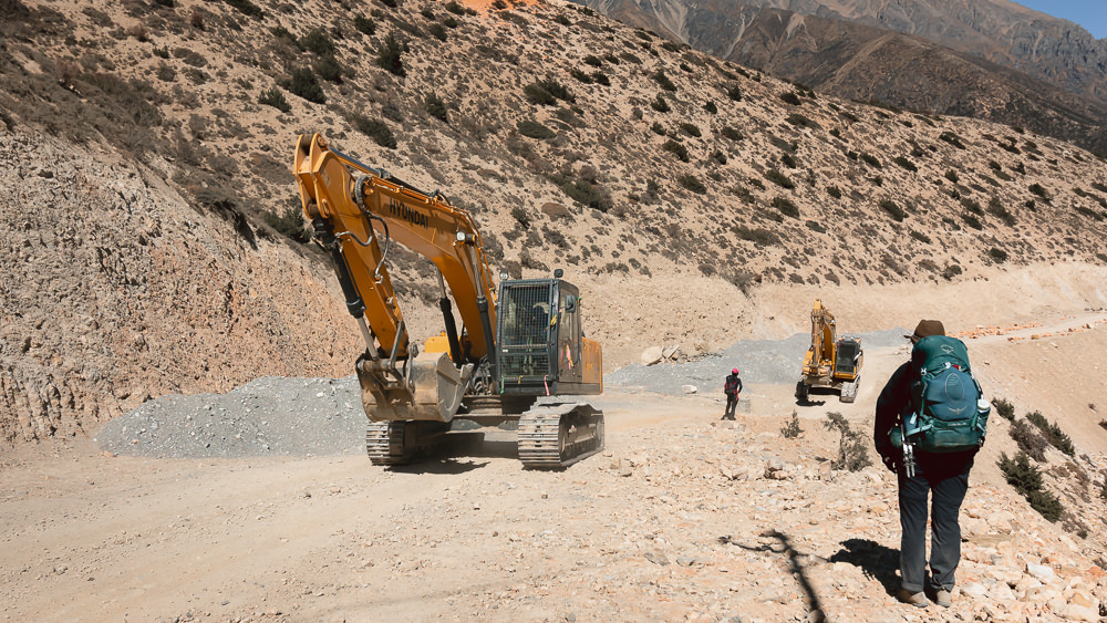 A hiker on the Upper Mustang trek is forced to wait at the side of the dirt road because of construction vehicles and ongoing work.