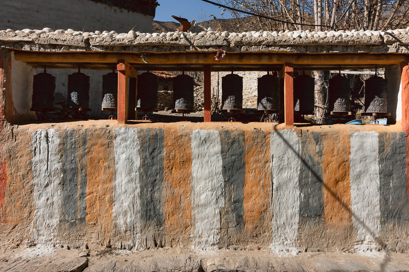 A wall of prayer wheels in the village of Tamagaon, painted with vertical white, grey and ochre stripes.