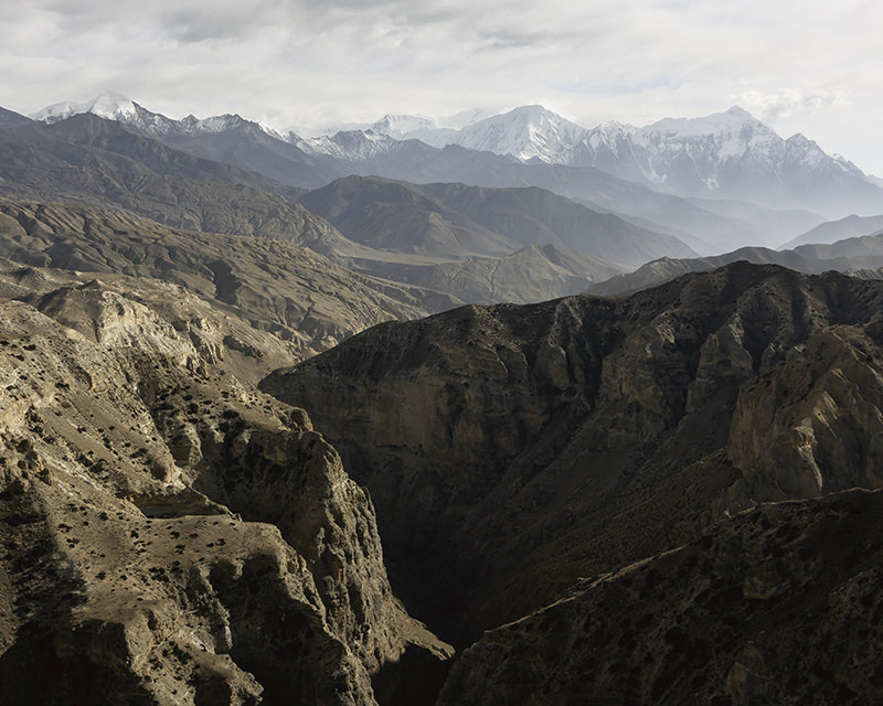 Deep canyons and ridges form a layered Upper Mustang landscape all the way back to the snowy peaks of the Annapurnas
