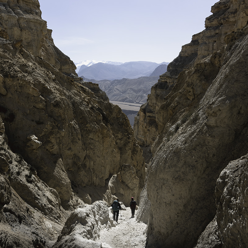 Two trekkers descending a narrow trail between high sided cliffs towards Dhi village in Upper Mustang