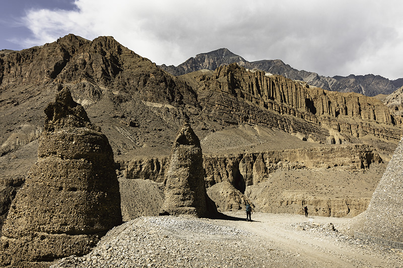 Two trekkers walk on a wide road during the first day of the Upper Mustang trek in Nepal, with strange rock pinnacles rising to the side and dramatic mountains seen behind.