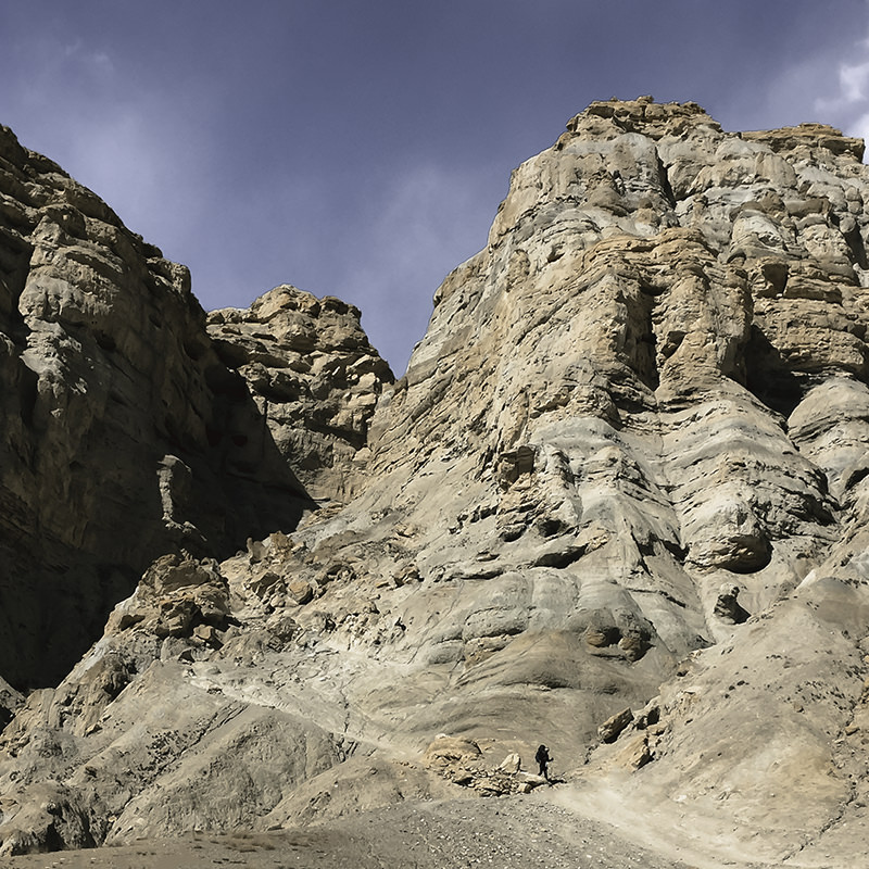 A trekker descending through a rocky canyon trail towards Dhi in Upper Mustang