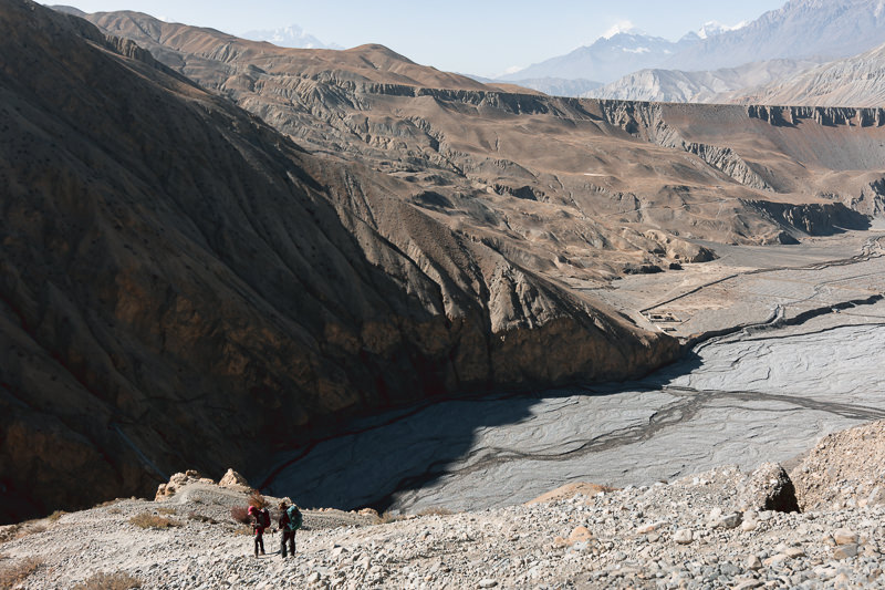 Two trekkers descending a steep and rocky trail towards the riverside village of Dhye in Upper Mustang
