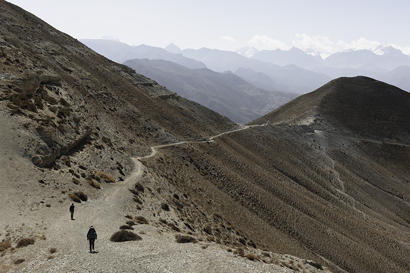 Two trekkers on a narrow trail stretching off into the distance on an Upper Mustang Trek