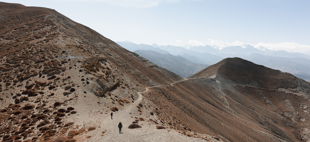 A panorama of two trekkers on a narrow trail stretching off into the distance on an Upper Mustang Trek