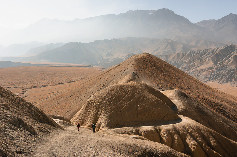 Trekkers on a trail approaching a round orange rock formation with a plateau stretched out into the distance in Upper Mustang