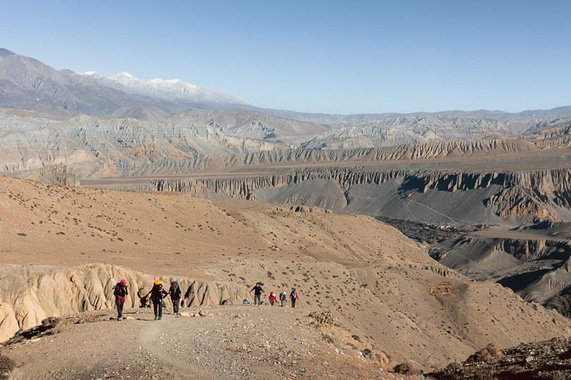 Trekkers climbing a long steep trail from Tangge on an Upper Mustang trek