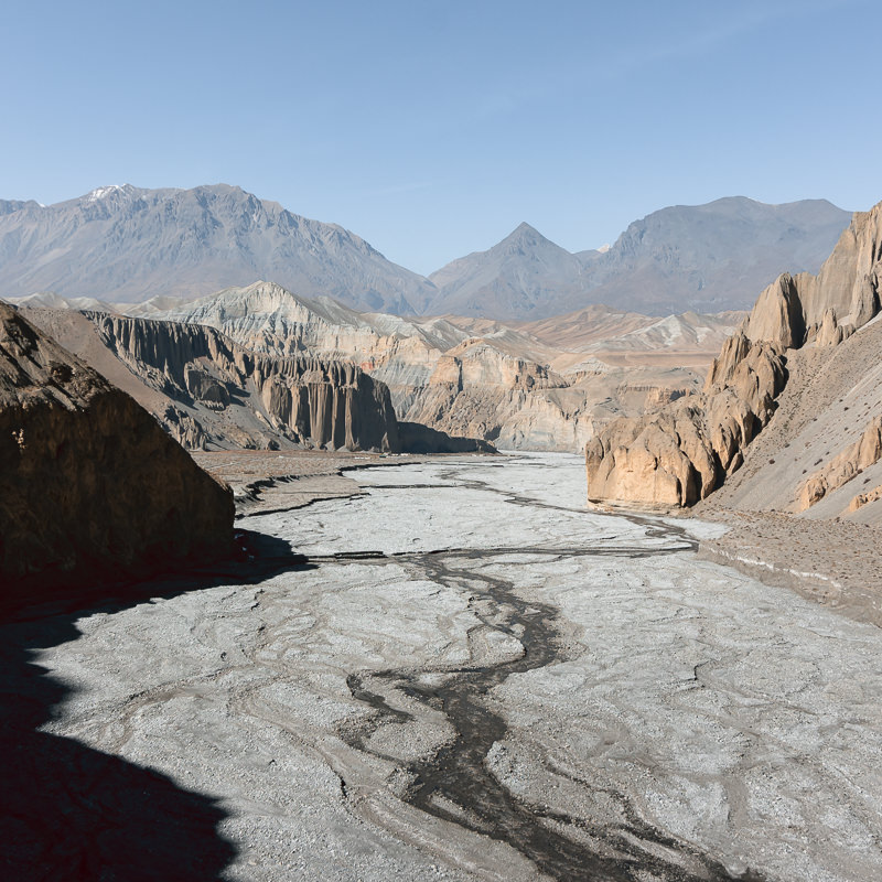 A view down the middle of the valley with jagged mountains rising on each side of a wide riverbed, as seen from the suspension bridge before Dhye in Upper Mustang