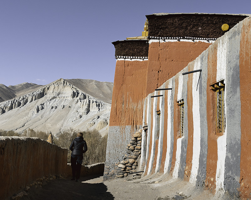 The striped walls and blocky red building of the 16th Century Tsarang Gompa in Upper Mustang