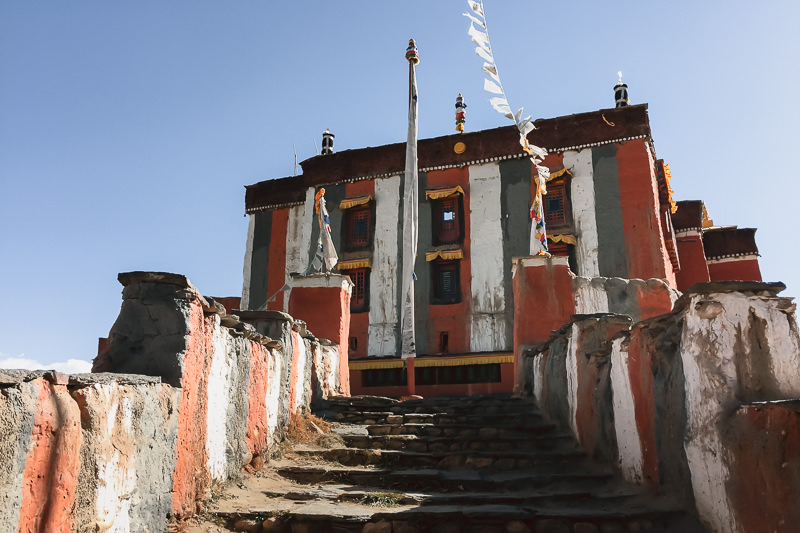 Looking up the stairs towards the striped walls of the large block shaped 16th Century Tsarang Gompa in Upper Mustang