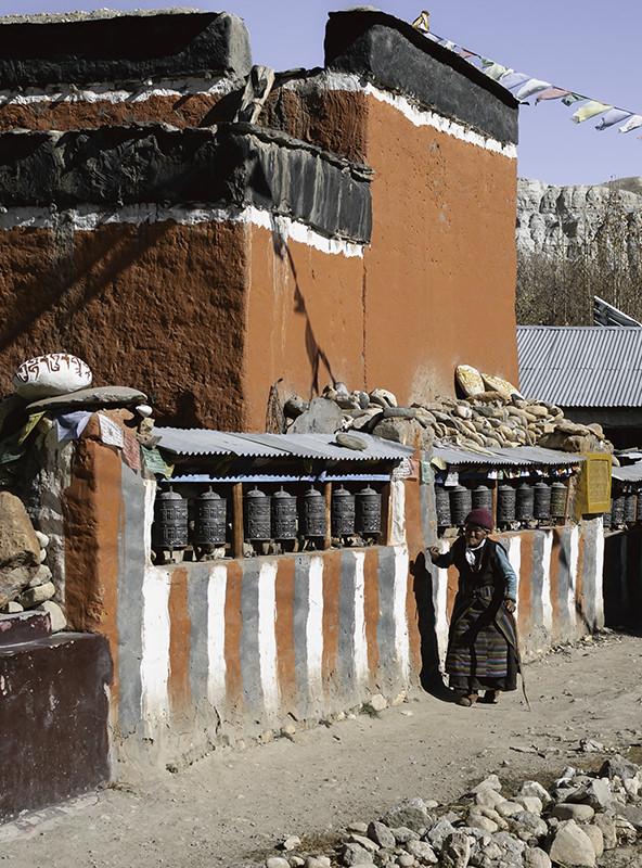 An elderly woman in traditional Tibetan dress spinning prayer wheels along a striped wall in Tsarang