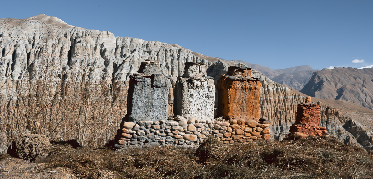 A Triple Protector (Rigsum Gonpo) statue in Tsarang with three columns in grey, white and orange, with similarly coloured mountains in the background
