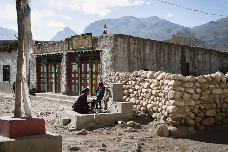 A woman doing laundry at a communal water tap in Tsarang while her young son looks on
