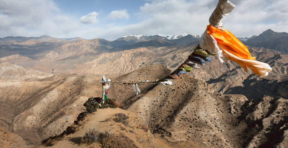 A line of prayer flags streaming in the wind at the Yamda Pass viewpoint on the Upper Mustang trek