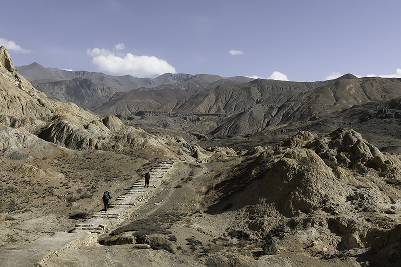 Two trekkers climbing a crumbling staircase towards the village of Yara on an Upper Mustang Trek