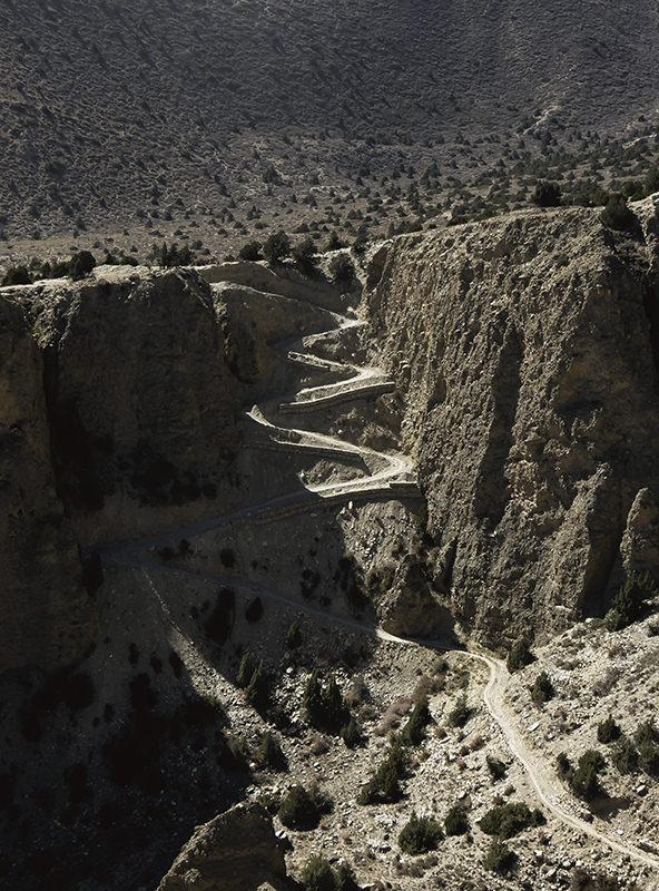 A switchback dirt trail descending a steep rock face on the Upper Mustang trek