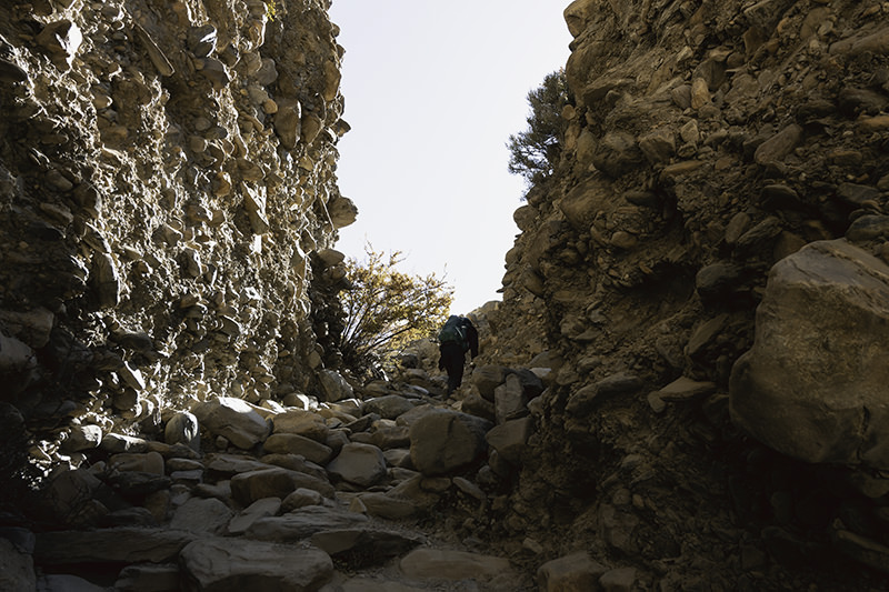 A trail of rough steps leads up between two rocky cliffs on the Upper Mustang trek.