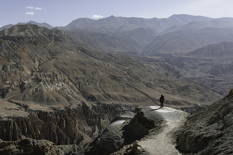 A trekker looking out to a vast expanse of colourful mountains and jagged rock formations on an Upper Mustang Trek