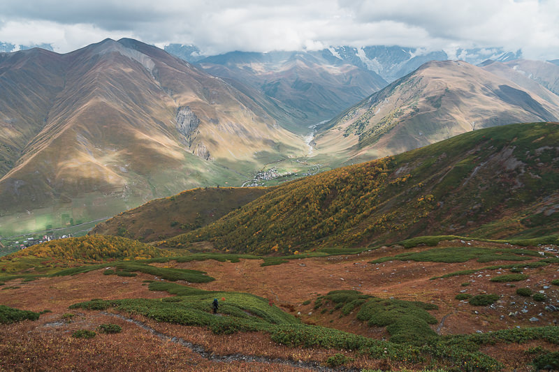 A hiker climbs through rhodedendrons on the way to Gorvashi Pass on the Ushguli to Chvelpi hike, with Ushguli tiny below Shkhara obscured by cloud