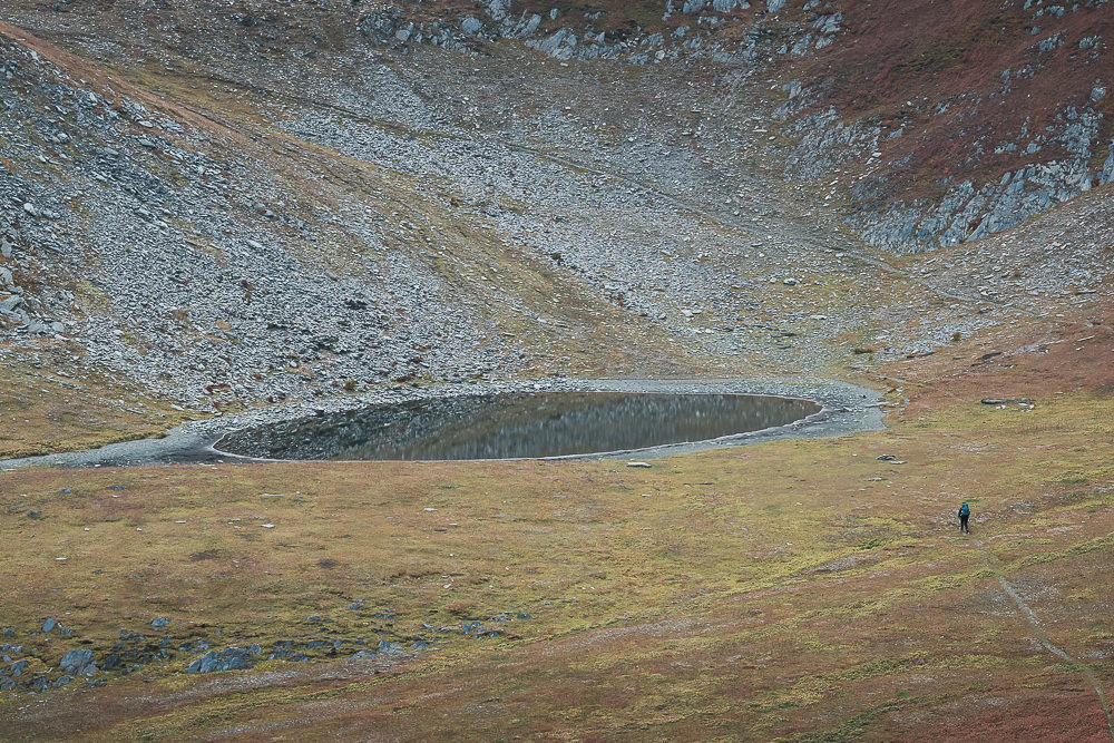 A hiker arrives at the first main lake on the ridge, the best place to camp on the Ushguli to Chvelpi hike