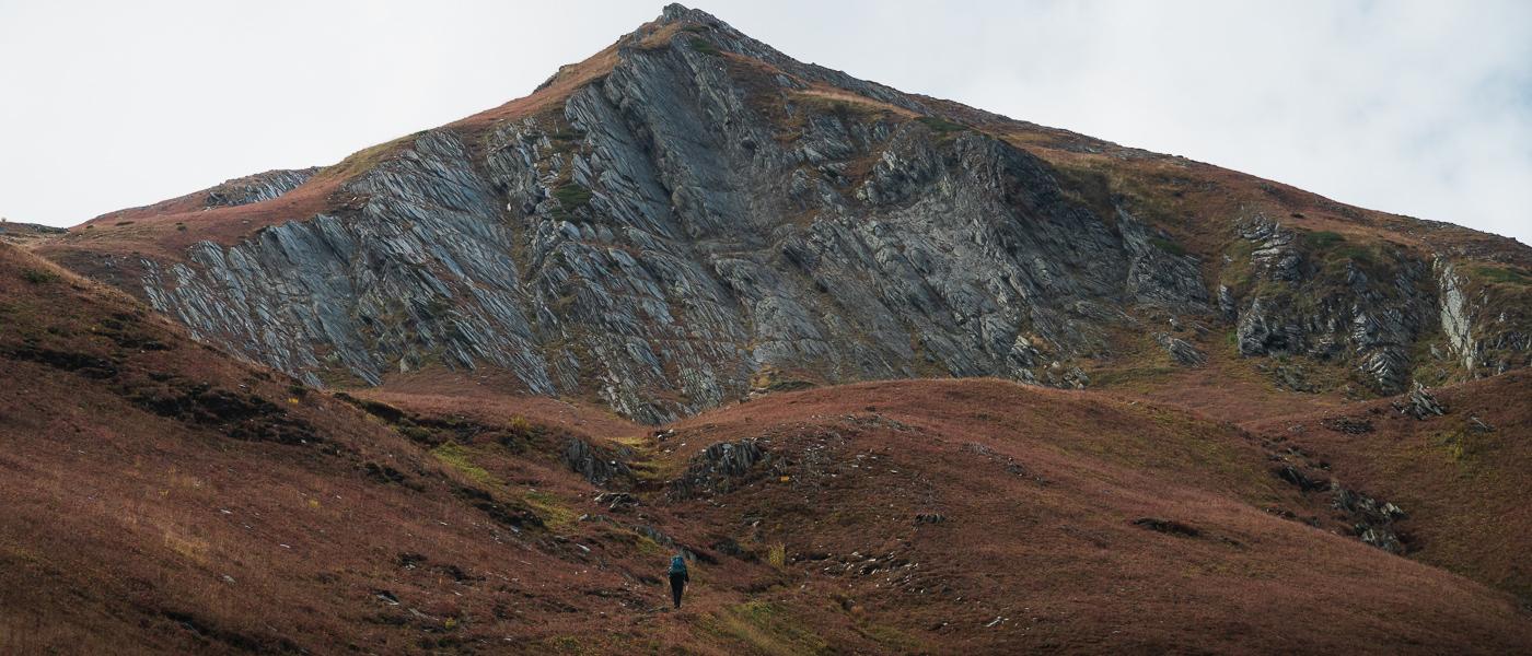 A hiker climbing along the ridge between Ushguli and Chvelpi