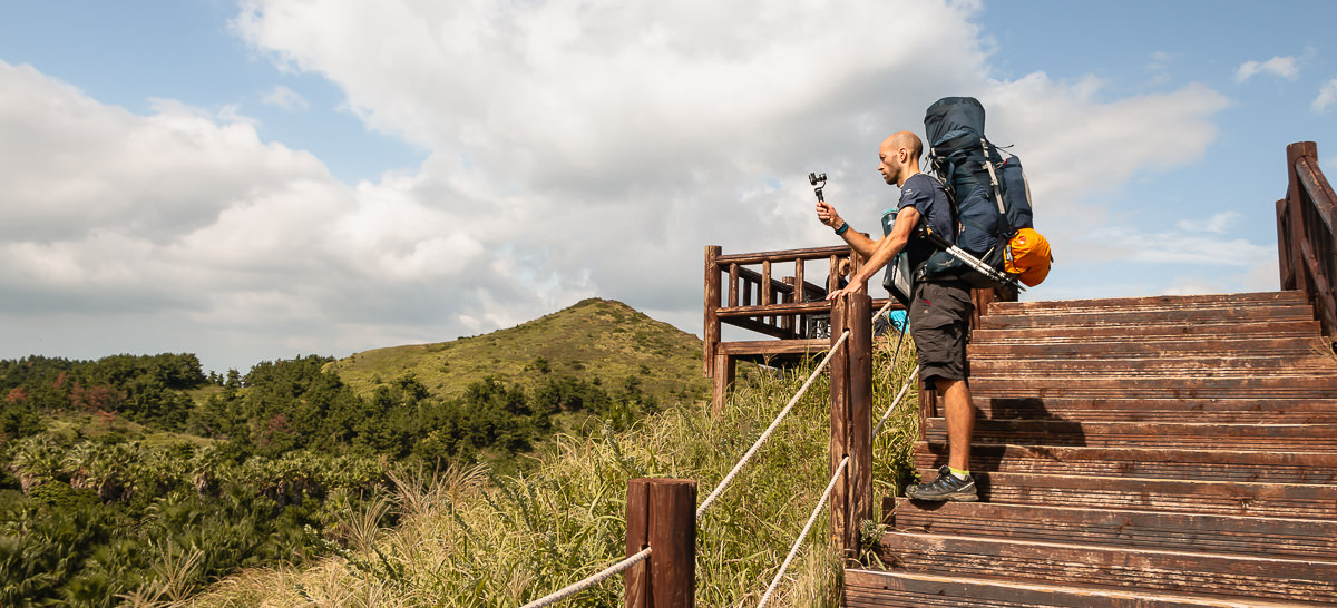 A hiker with a big backpack shoots video with Gopro and gimbal from a wooden walkway on the Jeju Olle Trail