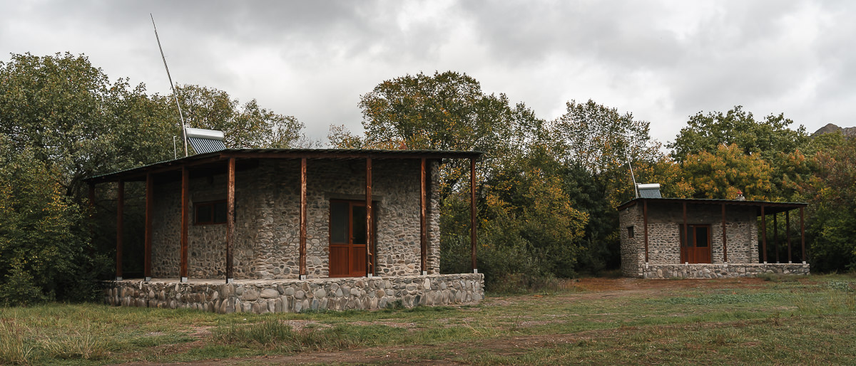 Two stone bungalows amidst the trees at Mijniskure in Vashlovani National Park