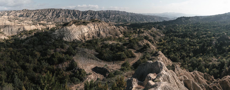 The winding dirt track descends through a badlands landscape towards Mijniskure in Vashlovani National Park