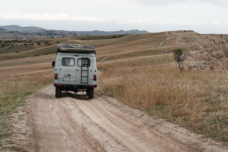 A UAZ Buhanka camper van follows a winding dirt track above cliffs in Vashlovani National Park