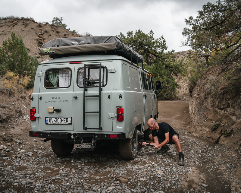 A person scrapes thick, clay-like mud from the tyres of a UAZ Buhanka camper van in Vashlovani National Park
