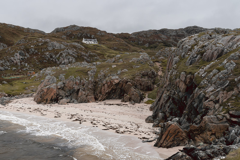The golden sand of Vestey's beach backed by dramatic rocks, mossy grass, and a white cottage. The beach is close to the popular Achmelvich beach on Scotland's North Coast 500 route.