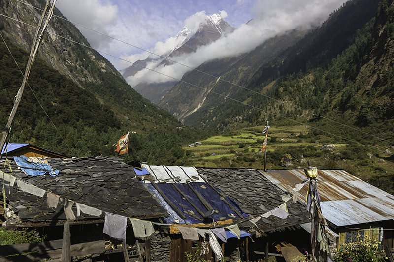 Mountain and valley views beyond rooftops in Namrung on the Manaslu Circuit