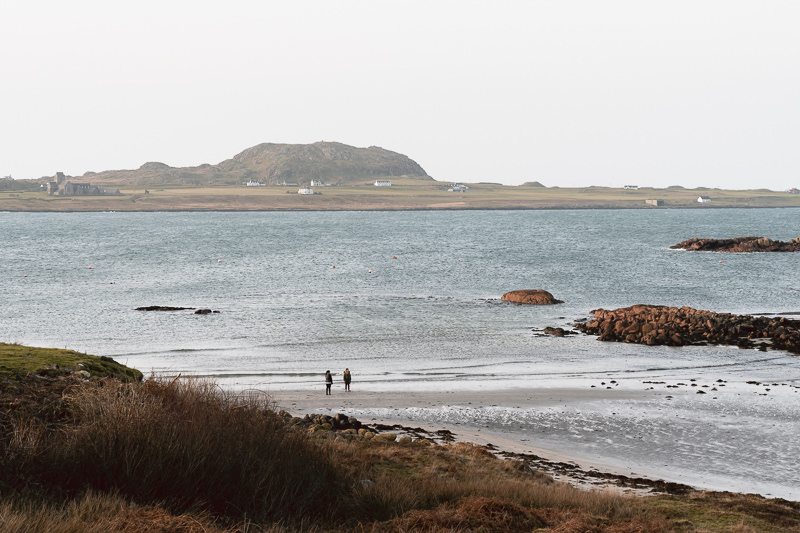 Two people walk on the beach at Fionnphort on the Isle of Mull. Behind them is Iona, where the famous abbey can be spotted near the shore.