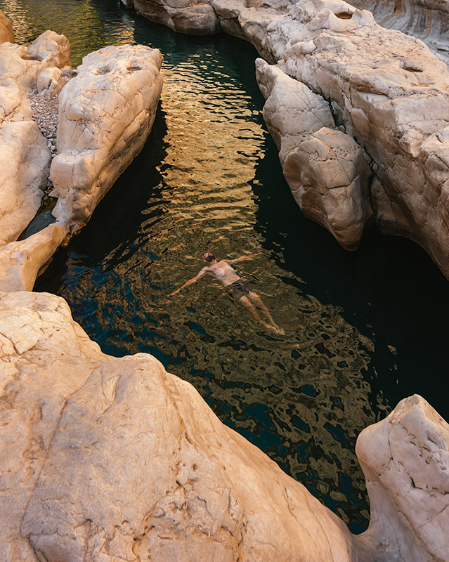 A person floating in one of the upper rock pools of Wadi Bani Khalid in Oman