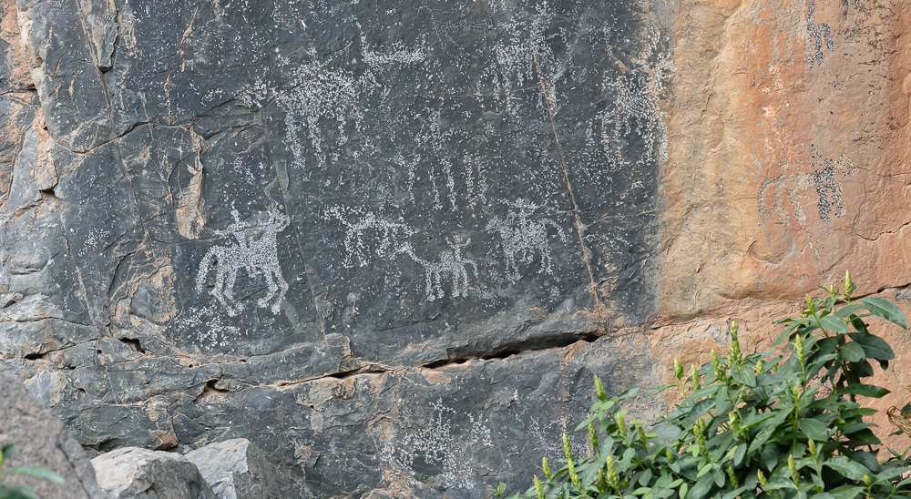 Rock carvings of people on animals on a cliffside at Wadi Damm in Oman, part of a 10 Day Oman Itinerary