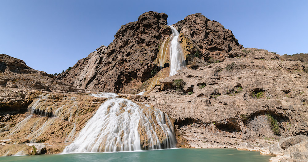 The waterfall at Wadi Darbat spilling down over the pockmarked rock face that is the travertine curtain