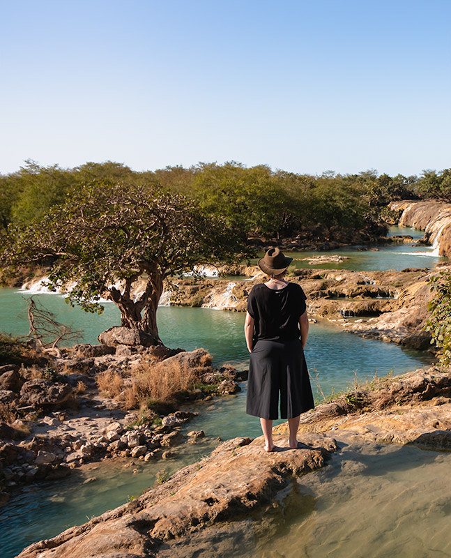 A person stands looking at the aquamarine rock pools of Wadi Darbat