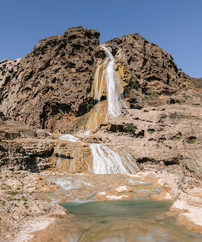 The three tiered waterfall of Wadi Darbat spilling down the pockmarked travetine curtain
