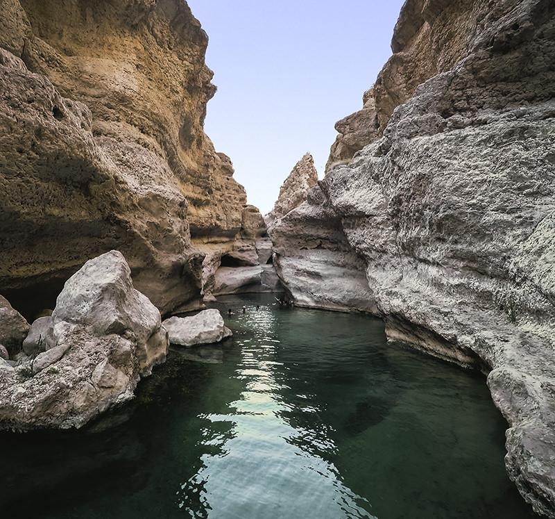 A green rock pool of Wadi Shab in Oman surrounded by high rock walls